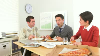 stock-footage-businessteam-eating-pizza-while-at-work